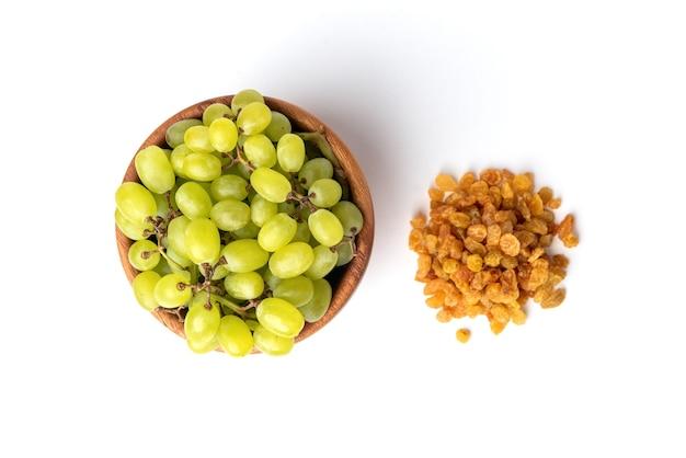 Rodzynki i zielony winogron na białym tle