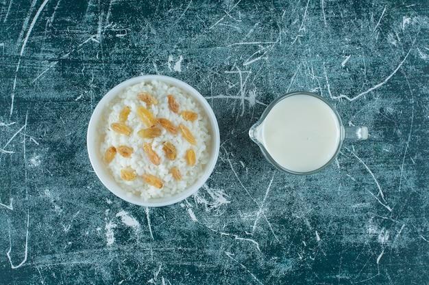 Rodzynki na misce ryżowego puddingu obok szklanki mleka na niebieskim stole.