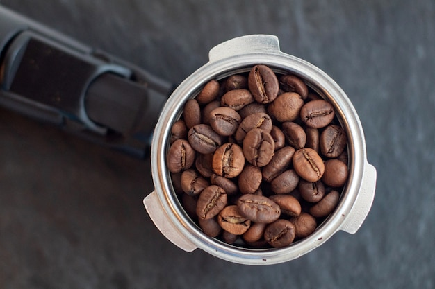 Róg z ziaren kawy. ekspres do kawy uchwyt na filtr z ziaren kawy na czarnej płycie łupkowej.