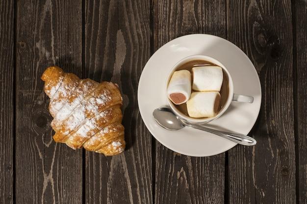 Rogalik bun z gorącą kawą z mlekiem i smacznymi piankami z czekoladą w białym kubku na ciemnym tle drewnianych. leżał na płasko.