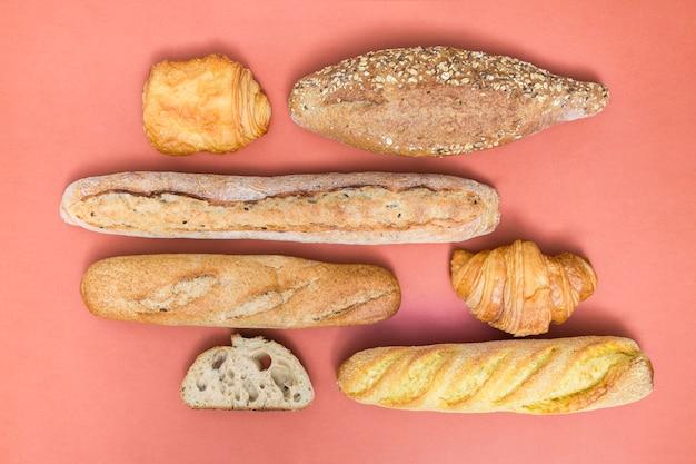 Rogalik; ciasto francuskie; bochenek chleba i bagietki na kolorowym tle