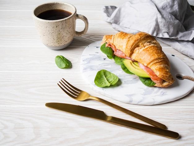 Rogalik francuski z plastrami łososia, awokado i szpinakiem na białej płycie ceramicznej oraz kubek czarnej kawy na drewnianym stole