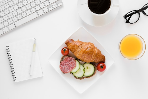 Rogalik i kanapka na talerzu z kawowym sokiem pomarańczowym i notatnikiem