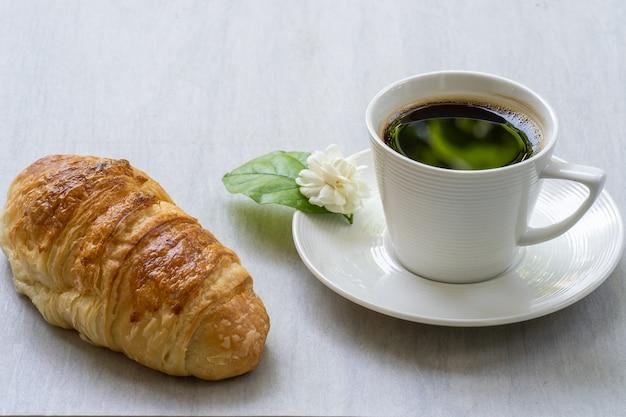 Rogalik i kawa na białym stole