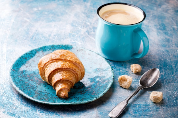 Rogalik i kawa z mlekiem. śniadanie świeże pieczenie.