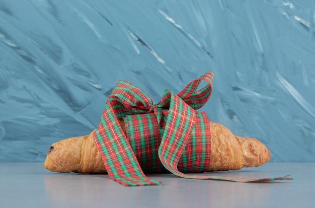 Rogalik przewiązany wstążką na marmurowym tle. wysokiej jakości zdjęcie