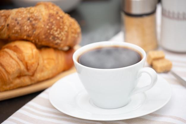 Rogalik śniadaniowy, cukier i gorąca kawa z mlekiem na stole