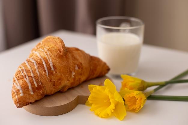 Rogalik, szklanka mleka i narcyz. wiosenne śniadanie młodej dziewczyny