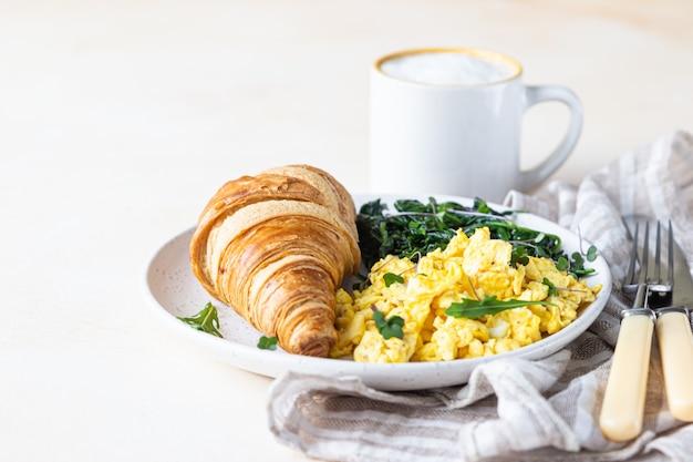 Rogalik z jajecznicą i szpinakiem na talerzu podawany z kawą. śniadanie.