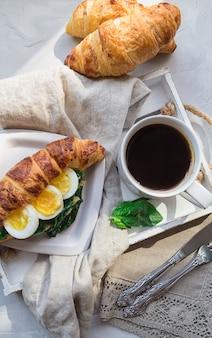 Rogalik z jajkiem i smażonym szpinakiem oraz kawą na drewnianej tacy na jasnoszarej betonowej powierzchni. zdrowe śniadanie. widok z góry.