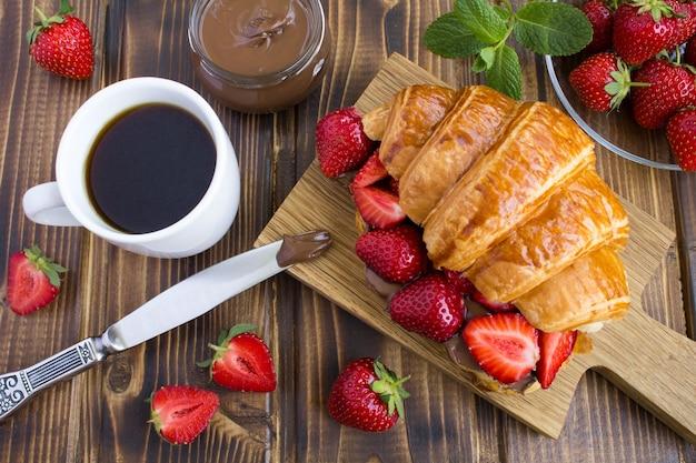 Rogalik z kremem czekoladowym i truskawką na drewnianej desce do krojenia. widok z góry.