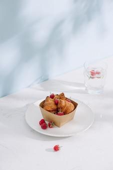 Rogalik z malinami. maliny z rogalikami. croissant na jasnym tle z malinowymi jagodami