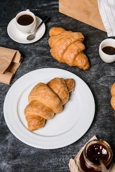 Rogaliki, garnek z dżemem i filiżanka kawy na bok na szarym stole