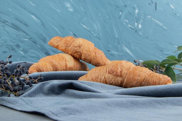 Rogaliki na ręczniku z winogronami na marmurowej podłodze, na marmurowym tle. wysokiej jakości zdjęcie