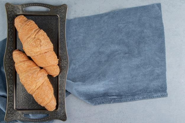 Rogaliki w tacach na ręczniku, na marmurowym tle. wysokiej jakości zdjęcie