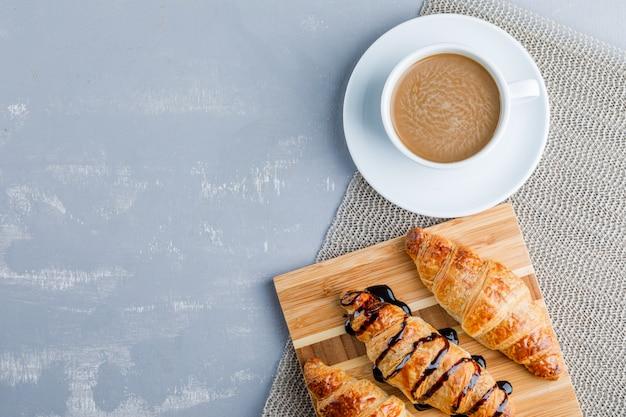 Rogaliki z kawą, deska do krojenia, leżak na płasko.