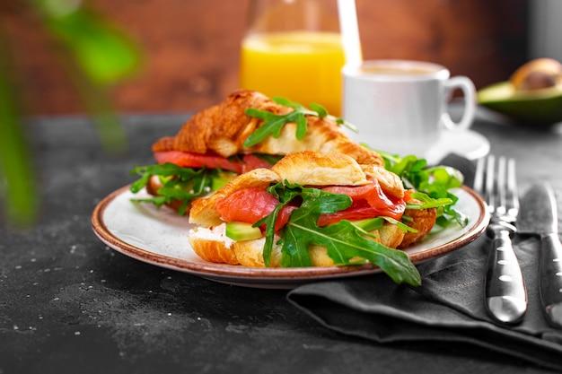Rogaliki z rukolą, awokado i łososiem, filiżanka czarnej kawy i szklanka soku pomarańczowego na stole