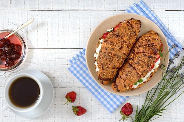 Rogaliki zbożowe z twarogiem i świeżymi truskawkami, filiżanką herbaty i dżemem. przydatne śniadanie. odpowiednie odżywianie. tradycyjne francuskie potrawy. widok z góry