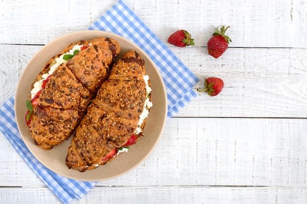 Rogaliki zbożowe z twarogiem i świeżymi truskawkami. przydatne śniadanie. odpowiednie odżywianie. tradycyjne francuskie potrawy. widok z góry