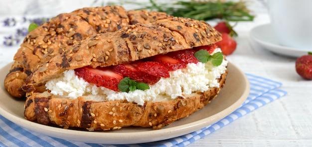 Rogaliki zbożowe z twarogiem i świeżymi truskawkami. przydatne śniadanie. odpowiednie odżywianie. tradycyjne francuskie potrawy.