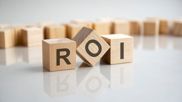 Roi - return on investment akronim koncepcja na kostkach, szare tło