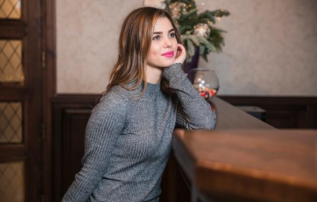 Rojenie uśmiechnięta młoda kobieta opiera na recepcyjnym biurku