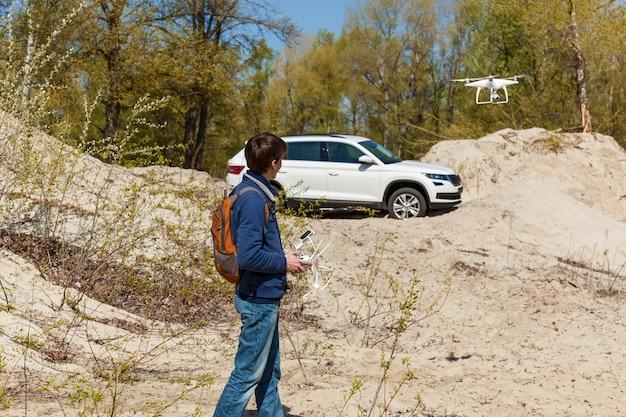 Rok modelowy 2017 kolega zarządza quadkopterem, który zdejmuje samochód z różnych skrótów perspektywicznych
