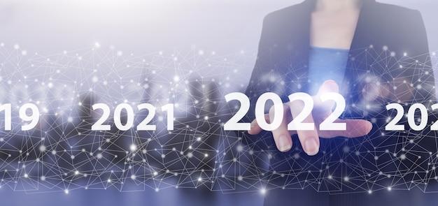 Rok załadunku 2021 do 2022. koncepcja startu. ręka dotykowy ekran cyfrowy hologram 2022 znak na światło miasta niewyraźne tło. nowy rok 2022, cel, plan, działanie.