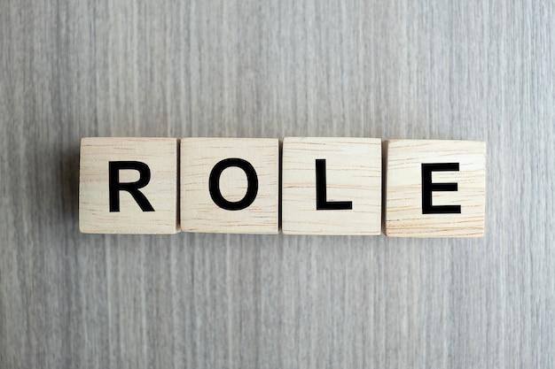 Rola biznesowy słowo konceptualny z drewnianym sześcianu blokiem na stołowym tle