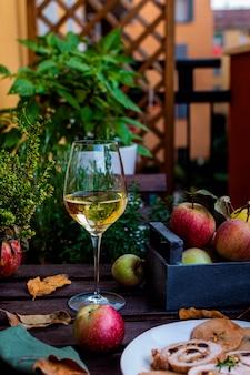 Rolada mięsna wypełniona pistacjami i suszonymi śliwkami, kieliszek białego wina na rustykalnym drewnianym stole