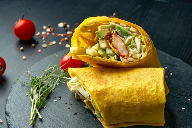 Roladka shawarma lub burrito z mango, krevektą, ogórkiem i sałatą. uliczne jedzenie