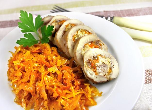 Roladka z kurczaka na parze z marchewką, serem i orzechami podawana na talerzu z pikantną duszoną kapustą