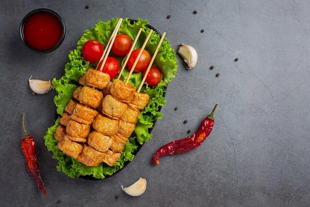 Roladka z kurczaka smażona w głębokim tłuszczu na ciemnej powierzchni.