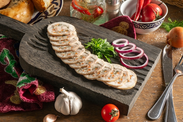 Roladka z kurczaka z serem suluguni, marchewką, ziołami, orzechami włoskimi, przyprawami, kolendrą i czerwoną cebulą, posiekana i podana na drewnianej desce do krojenia.