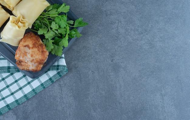 Roladki gotowane ciasto i pieczony kurczak na ciemnej desce.