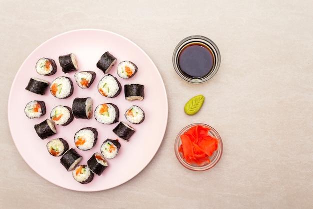 Roladki maki z imbirem, wasabi i sosem sojowym na różowym talerzu