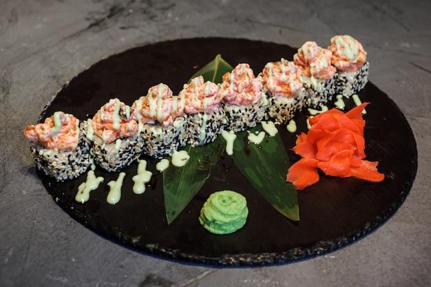 Roladki ryżowe fusion, maki sushi na czarnym talerzu z wasabi i imbirem.