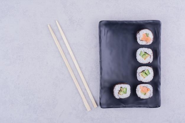 Roladki sake maki z łososiem i awokado na czarnym talerzu ceramicznym.
