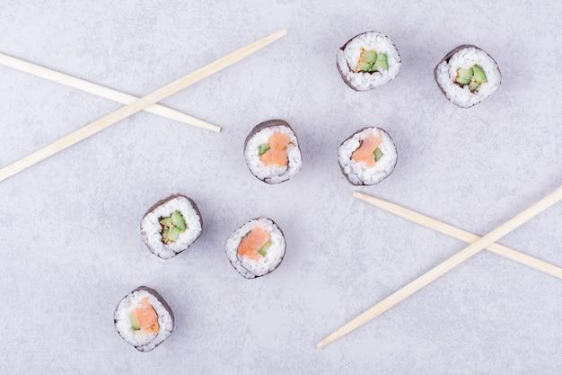 Roladki sake maki z łososiem i awokado na szaro.