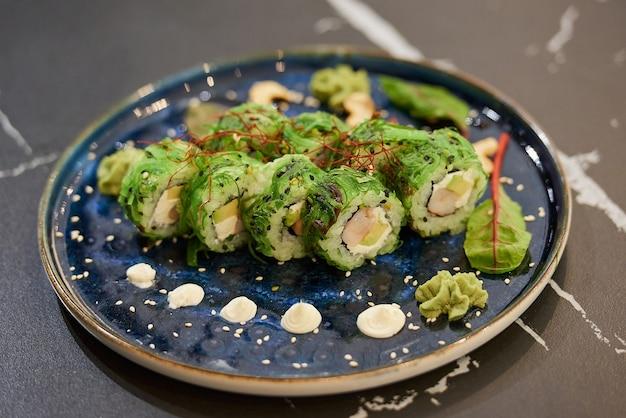 Roladki sushi na talerzu ceramicznym z sosem, orzechami nerkowca i wasabi na stole z czarnego marmuru