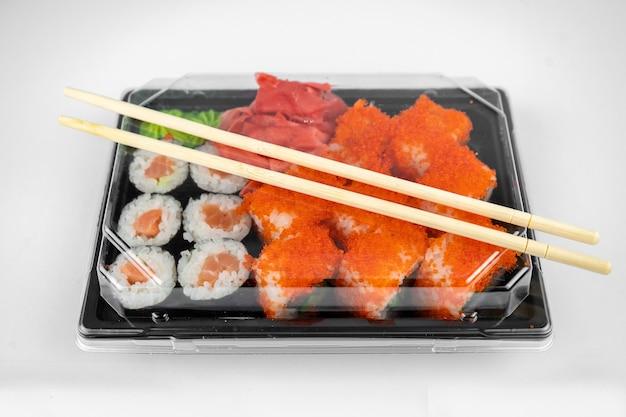 Roladki sushi na wynos w plastikowym pojemniku, kalifornia, rolka łosoś maki, różowy imbir, wasabi. koncepcja dostawy sushi