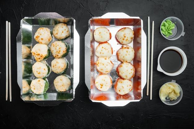 Roladki sushi na wynos w pojemnikach, roladki philadelphia i pieczone bułeczki z krewetkami ustawione na czarnym kamieniu