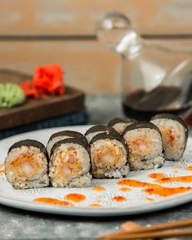 Roladki sushi nori z krewetkami przyozdobione słodkim sosem chili