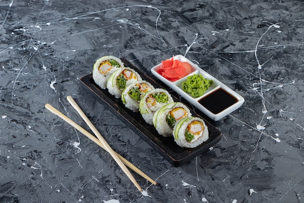 Roladki sushi ogórkowe z paluszkami krabowymi na czarnym talerzu.