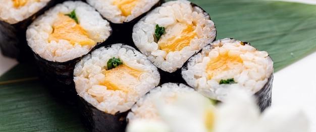 Roladki sushi podawane na drewnianym talerzu w restauracji wysokiej jakości zdjęcie