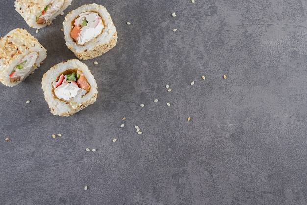 Roladki sushi, sos sojowy, wasabi i marynowany imbir na kamiennym tle.