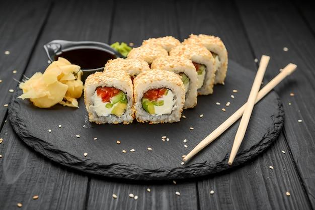 Roladki sushi w sezamie z awokado, łososiem i twarogiem na czarnym tle