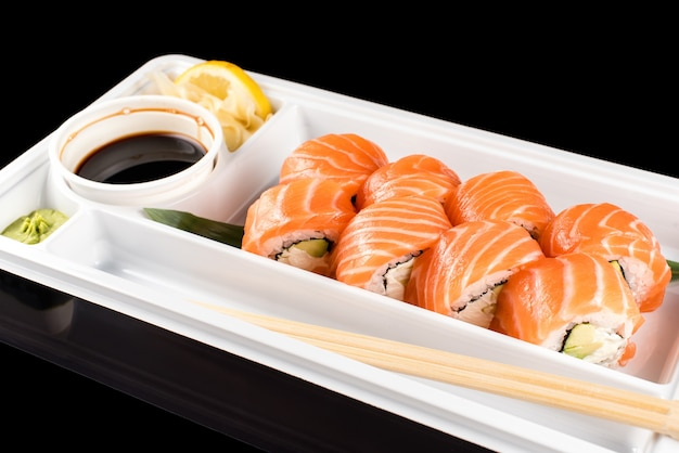Roladki sushi wykonane ze świeżego surowego łososia, twarogu i awokado w białym plastikowym pojemniku gotowe do spożycia na czarnym tle z odbiciami
