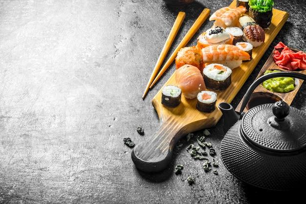 Roladki sushi z łososiem, krewetkami i twarogiem. na ciemnym tle rustykalnym