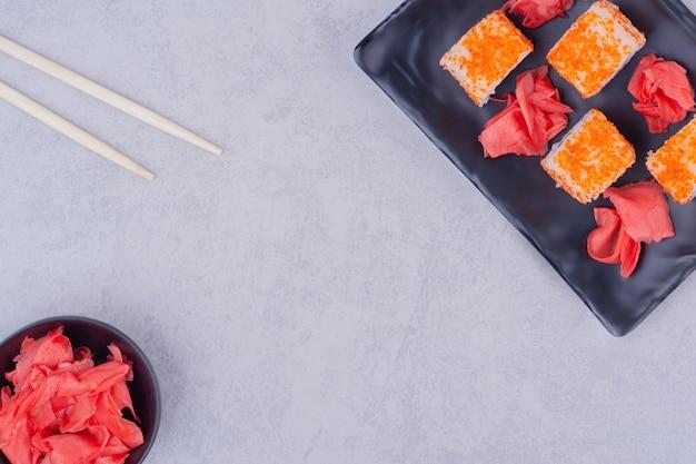 Roladki sushi z łososiem na czarnych ceramicznych półmiskach